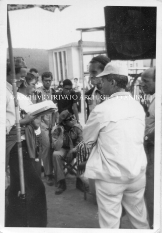 Seduto al centro Adriano Celentano ed in piedi con il cappello scuro Pietro Germi
