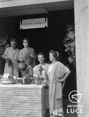 Archivio Storico Luce, Reparto Attualità (1927-1955), A00024661, Roma, Giornata nazionale dell'uva, 28 settembre 1930. Ricostruzione di una bottega di uve da tavola dell'antica Roma ai Mercati di Traiano, con donne e uomini vestiti da antichi romani.