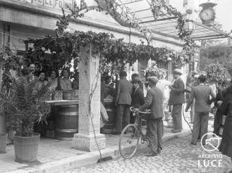 Archivio Storico Luce, Reparto Attualità (1927-1955), A00024667, Roma, Giornata nazionale dell'uva, 28 settembre 1930. Persone in fila presso il banco di vendita di uva da tavola allestito sotto la tettoia della Casa del Passeggero.